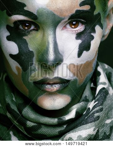 Beautiful young fashion woman with military style clothing and face paint make-up, khaki colors close up