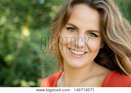 Beautiful woman with blue eyes dressed in red on a sunny day outside
