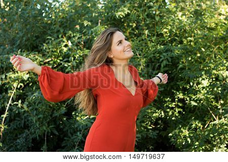 Beautiful woman dressed in red relaxed in nature