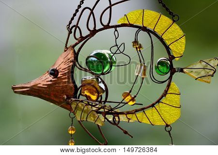 Detail of a craft product made of glass and copper wire in the shape of a fish