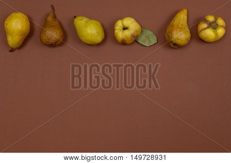 Green pears and quince in row on brown background with copy space