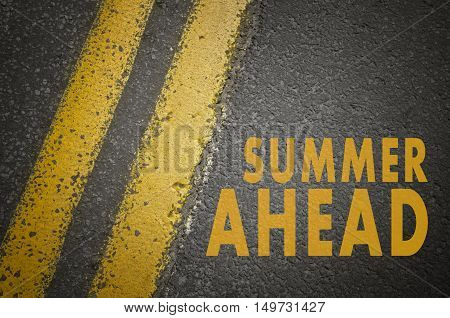 Summer concept. Summer ahead written on asphalt road.