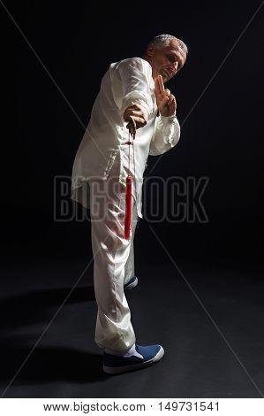 Senior man enjoys practicing Tai Chi with sword indoor.