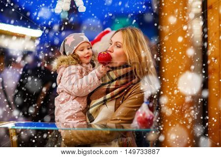 Beatiful woman and little kdi girl eating crystallized sugared apple on German Christmas market. Happy family in winter clothes with lights on background. Tradition, holiday concept