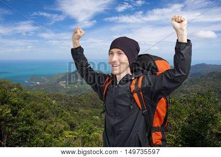 Happy male backpacker on background of ocean.