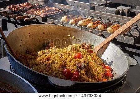 Rice with meat and vegetables (tomatoes hot peppers garlic carrots) in a large vat. In the background grilled meat and meat on the dough