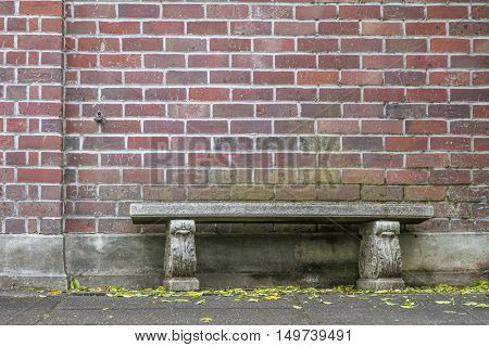 Old vintage brick wall background with a stone garden bench.