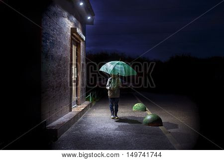 child with an umbrella in the dark. boy walking down the street at night. empty space for your text