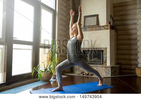 Full length portrait of attractive young woman working out at home in living room, doing yoga or pilates exercise on blue mat, standing in Warrior I posture, Virabhadrasana 1 pose