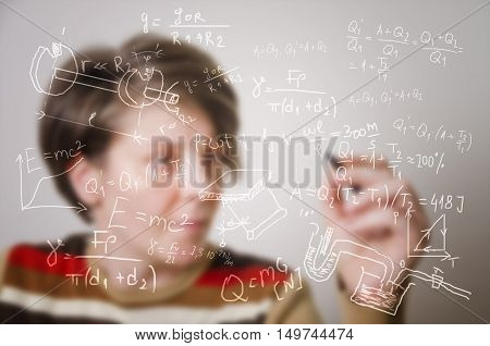 Blurred student writing formulas on transparent board