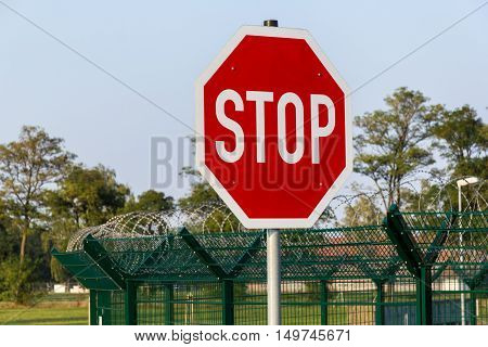 german stop sign on barb wire fence