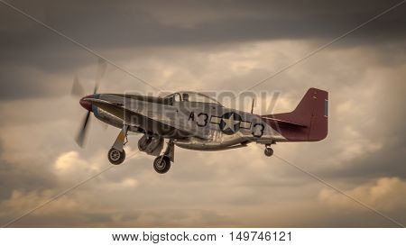 Farnborough, UK - 6th July 2016: A veteran P51 Mustang in flight at twilight after taking off from the airport