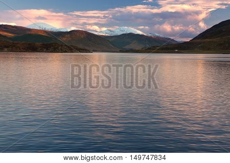 Snowcapped mountains by the sea at sunset at Ullapool Scotland