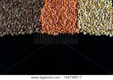 Varied diferent lentils pulses,mixed in the studio table,  with negative space bottom.