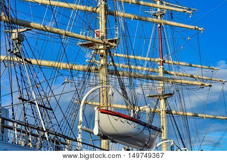 Crows nest mast and canvas sails can be seen in this closeup detail of an old time tall wooden sailing ship.