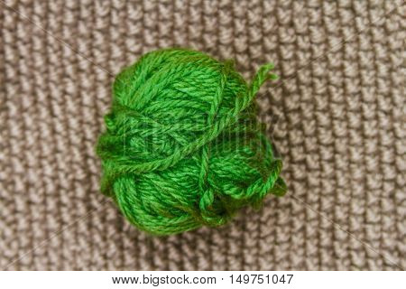 Green Ball Of Wool On Beige Cloth Woven Wool