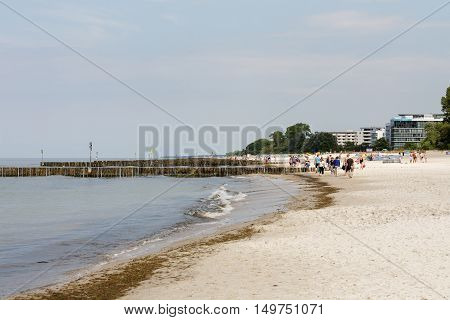 KOLOBRZEG POLAND - JUNE 19 2016: Unidentified sunbathers enjoy a sunny day on the sandy beach and they are walking along the coast of the Baltic Sea in which there are wooden breakwaters