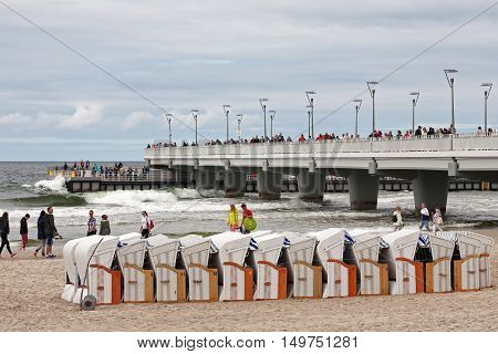 KOLOBRZEG POLAND - JUNE 26 2016: Unidentified tourists enjoy their leisure time strolling along the shore of the Baltic Sea many people enjoy the views from the pier projecting into the sea