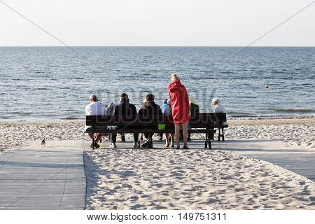 KOLOBRZEG POLAND - JUNE 20 2016: Unidentified vacationers have a rest on benches that was set on the sandy beach looking at the vastness of the waters of the Baltic Sea