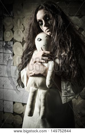 Horror style shot: a strange sad girl with moppet doll in hands