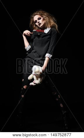 Horror shot: a scary monster girl with rabbit toy and bloody cleaver in hands