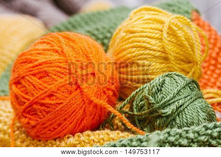 Three Yellow, Orange And Green Balls Of Wool On Color Wool Fabric
