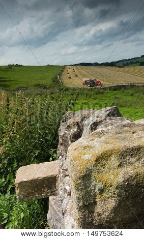 A hay baler at work in a field in the countryside with a rock wall in the foreground