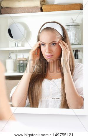 Beautiful young woman massaging her temporal at home