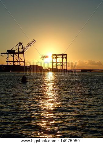 Sunset through Hoisting cranes at container cargo terminals with Bridge on Sand Island on Oahu Hawaii.