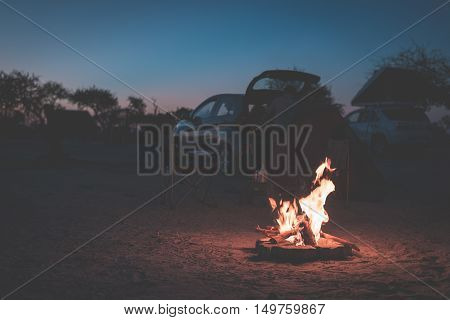 Burning Camp Fire At Dusk In Camping Site, Botswana, Africa. Summer Adventures And Exploration In Th