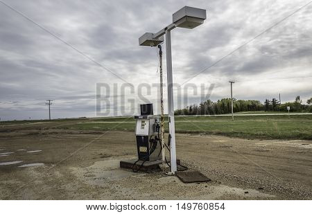 horizontal image of an old gas station pump standing under broken lights sitting next to a highway on a wet gravel surface under a rainy grey cloudy sky in the summertime