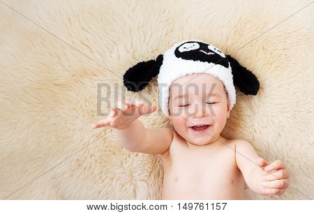 sleepy one year old baby lying in sheep hat on lamb wool background