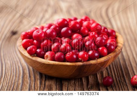 Cowberries, red bilberries, cranberries in a rustic bowl on a wooden background