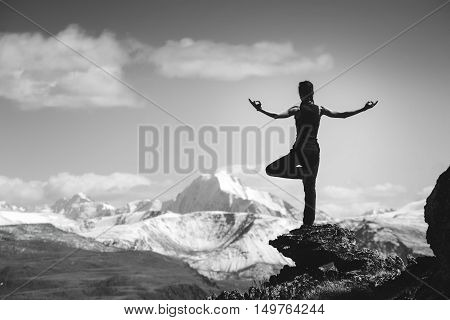 Woman stands in yoga pose on big rock on background of mountains