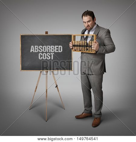 Absorbed cost text on blackboard with businessman and abacus