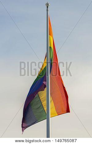 The Rainbow Flag on a Flagpole with a partly cloudy sky.