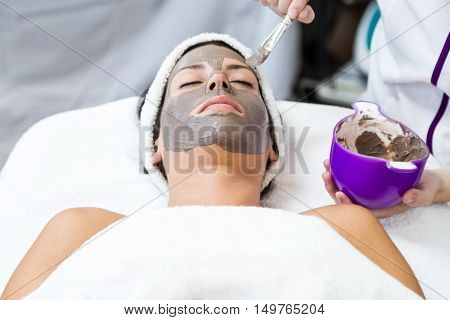 Beautiful Young Woman With Clay Facial Mask In Beauty Spa. Detox Ritual.