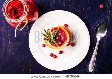 Winter one bite-sized snack or dessert: tartlets with sweet and sour cranberry sauce, decorated with rosemary. Top view