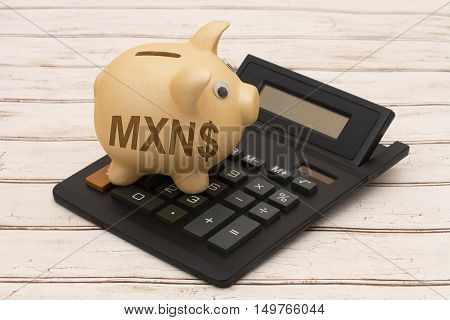 The MXN dollar currency A golden piggy bank and calculator on a wood background with symbol of dollar sign and text MXN