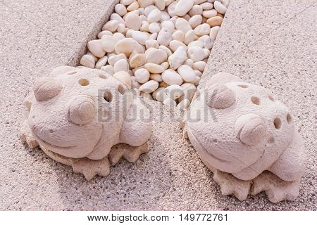 Twin frogs statue made by limestone at pool gutter