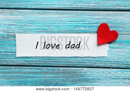 Red heart and sheet of blank paper on a blue wooden table, i love dad
