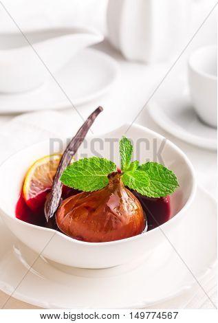 Poached fig in red wine with vanilla and mint on table