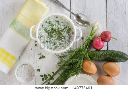 Okroshka soup with ingredients vegetables radish onion dill and eggs on a white table