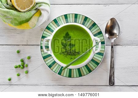 Green pea soup garnished with greens and onion