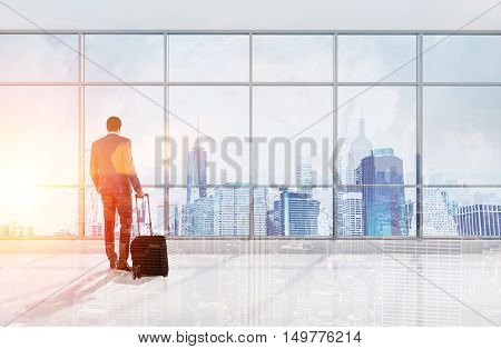 Rear view of African American man with suitcase looking at large city panorama through office window. Concept of transition to other department in different city. Toned image