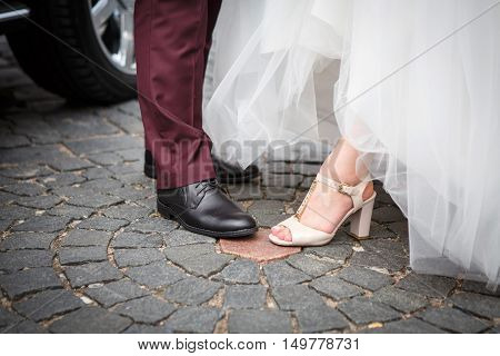 Feet in shoes of the bride and groom on the old cobblestones. Wedding clothing newly married.