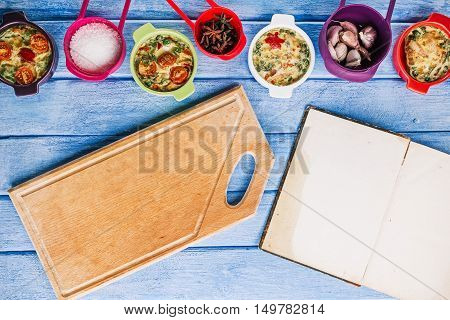 Scrambled eggs baked with fillings in mini ceramic forms, spices and cutting board