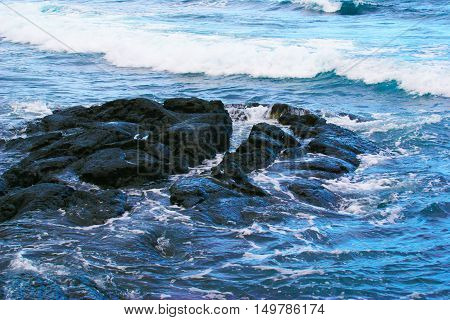 Rocky beach in Maui, Hawaii with medium waves.