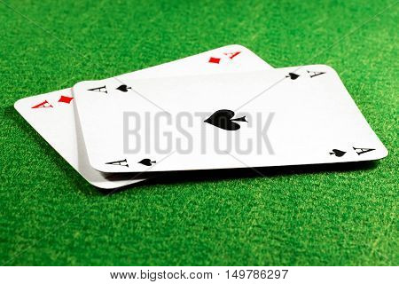 Two aces on green felt casino table ace of spades on top. Selective focus on the spade symbol