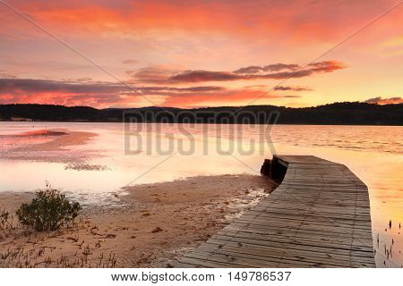 Vibrant Skies And Curved Jetty